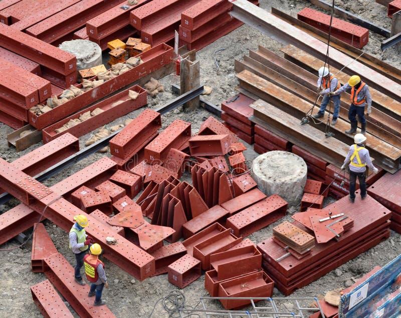Bouwvakkers en ingenieurs die veiligheidshelm en eenvormig concentraat bij het opheffen van rood structureel staal door een sling stock afbeeldingen