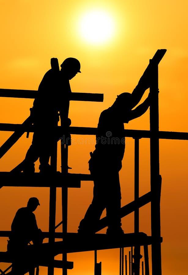 Bouwvakkers onder een hete opvlammende zon stock afbeelding
