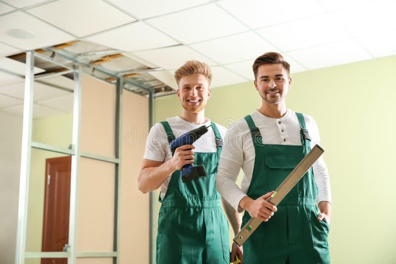 Bouwvakkers in uniformen De dienst van de huisreparatie stock afbeelding