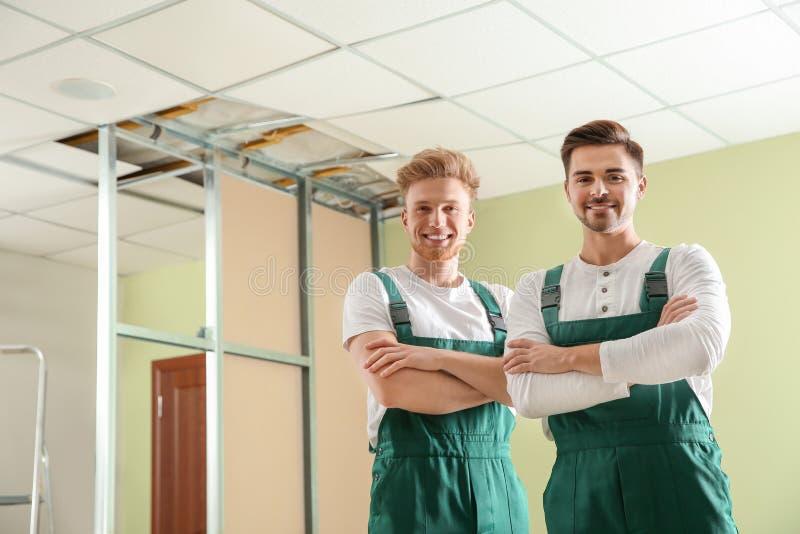 Bouwvakkers in uniformen De dienst van de huisreparatie royalty-vrije stock foto