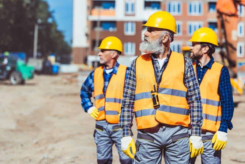 Bouwvakkers in weerspiegelende vesten en bouwvakkers die, onderzoeken zich buiten bevinden stock foto's
