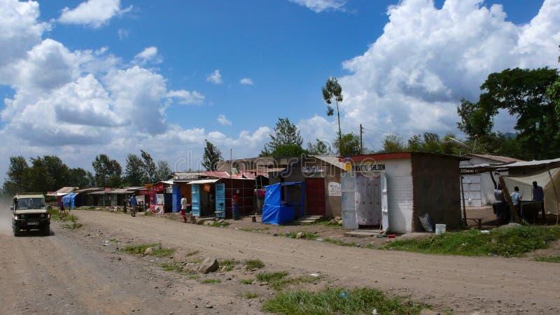 Bouwvallig die dorp van gerecycleerde materialen op de kant van de weg in Tanzania met winkels en kleine huizen voor plaatselijke royalty-vrije stock foto