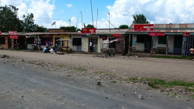 Bouwvallig dorp dat van gerecycleerde materialen op de kant van de weg in Tanzania met winkels en kleine huizen voor plaatselijke stock afbeeldingen