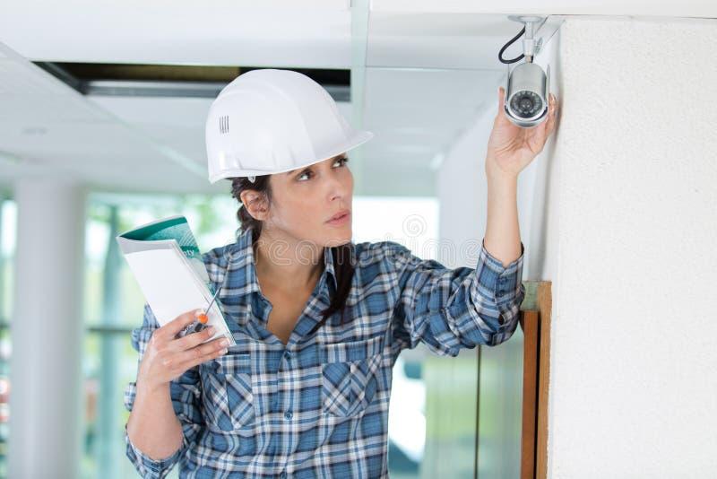 Bouwvrouwelijke werknemer die met ladder kabeltelevisie-installatie controleren stock afbeeldingen