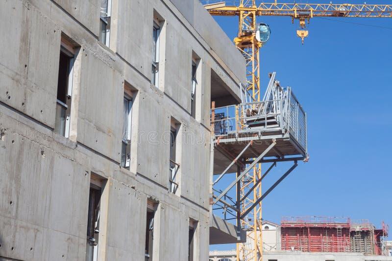 Bouwwerf in Frankrijk van een woningbouw, met scaffholdings, concrete voorgevels en cementblokken, evenals kranen royalty-vrije stock fotografie