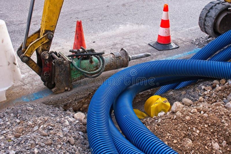 Bouwwerf, het wegwerk Hydraulische verpletterende hamer Plastic pijpen voor elektrische kabels stock foto