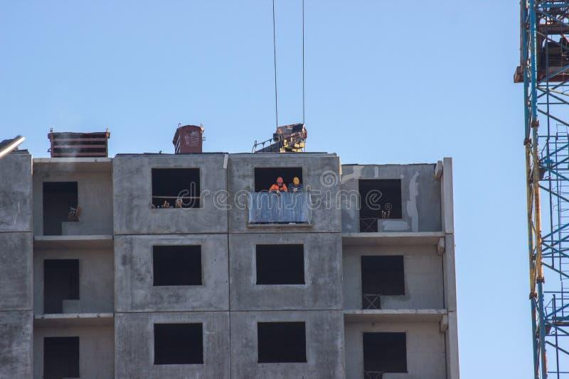 Bouwwerf met kraan Verscheidene kranen werken aan de bouw complex tegen de blauwe hemel een groep bouwers stock afbeelding