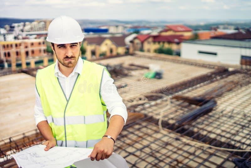Bouwwerf, portret van de mens die bouwvakker en veiligheidsmateriaal op bouwterrein dragen stock fotografie