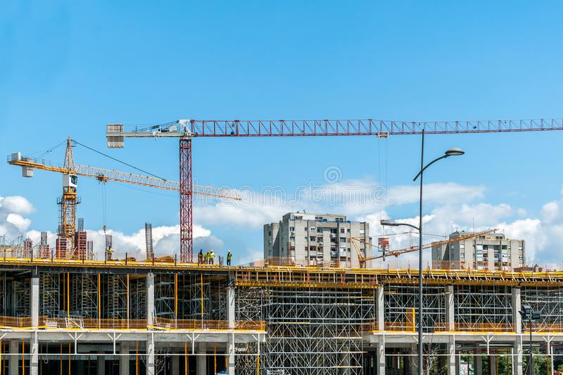Bouwwerf van nieuw wandelgalerij of winkelcentrum in de stad met kranenmachines, steiger, concreet met staalversterking stock foto