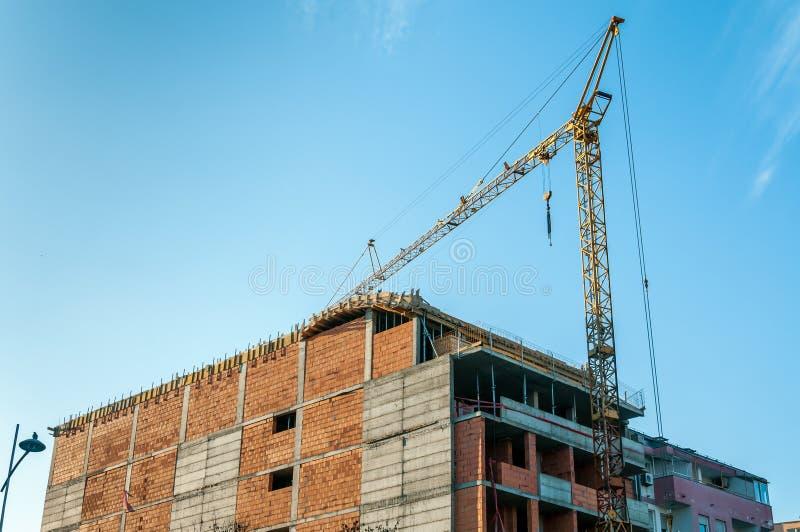 Bouwwerf van nieuwe woningbouw met flats en bureaus met kraan en steigers tegen blauwe hemel stock foto