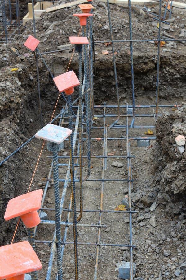 Bouwwerfmening van oranje rebar veiligheidskappen op net van st stock afbeeldingen