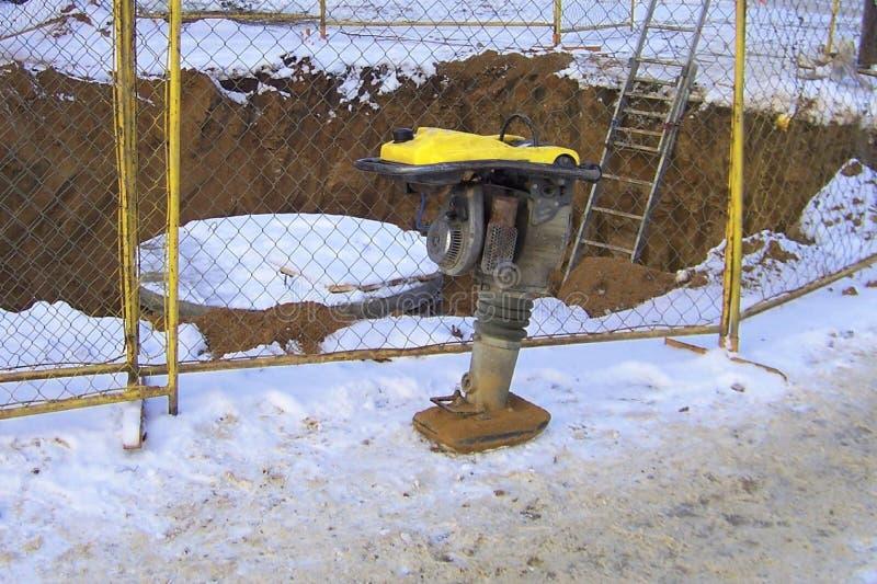 Bouwwerkzaamheden, bouwhulpmiddel, benzine vibrorammer, gronddichtingsproduct, de winter, stock foto