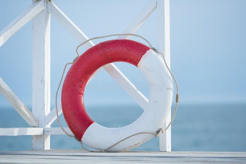 Bouy floater för rött och vitt liv på träbron på en havssida royaltyfria bilder