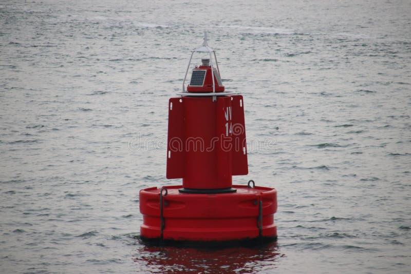 Bouy rosso sul Nieuwe Waterweg al porto di Rotterdam per segnare l'itinerario di spedizione immagini stock