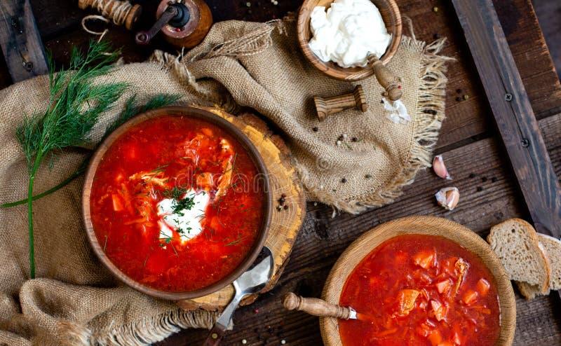 Boven geschoten van twee houten kommen met smakelijke Oekra?ense of Russische traditionele bietensoep borscht met zure room stock foto's