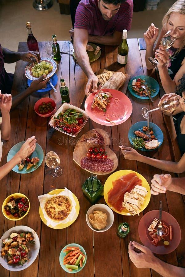Boven geschoten van vrienden die voedsel over een dinerlijst overgaan stock foto