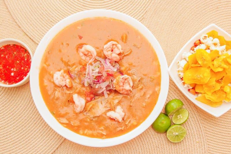 Boven mening van Ecuatoriaans voedsel: garnalen cebiche met sommige chifles binnen witte kom, citroen en rode kruidige salade bin royalty-vrije stock afbeelding