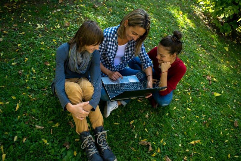 Boven mening van gelukkige moeder en kinderen die computer in het park met behulp van royalty-vrije stock foto