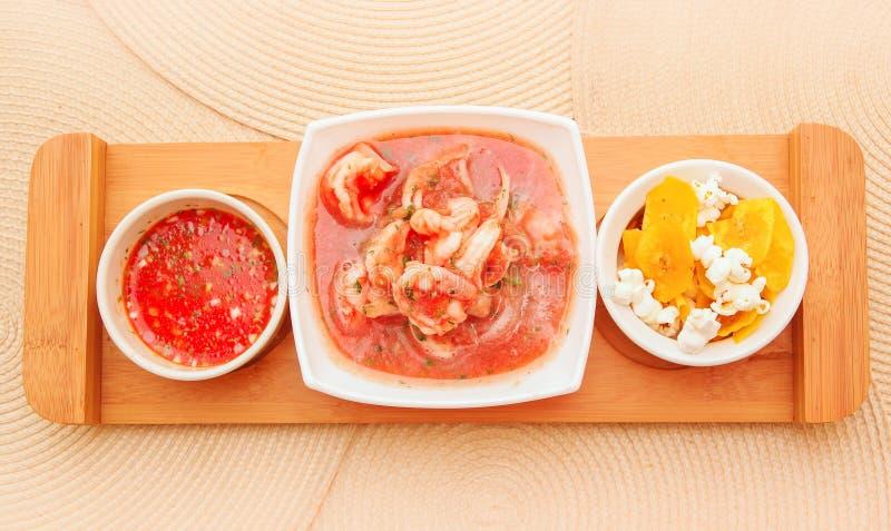 Boven mening van heerlijke garnalen cebiche in rechthoekige witte kom diende met chifles en rode kruidige saus over houten royalty-vrije stock foto's