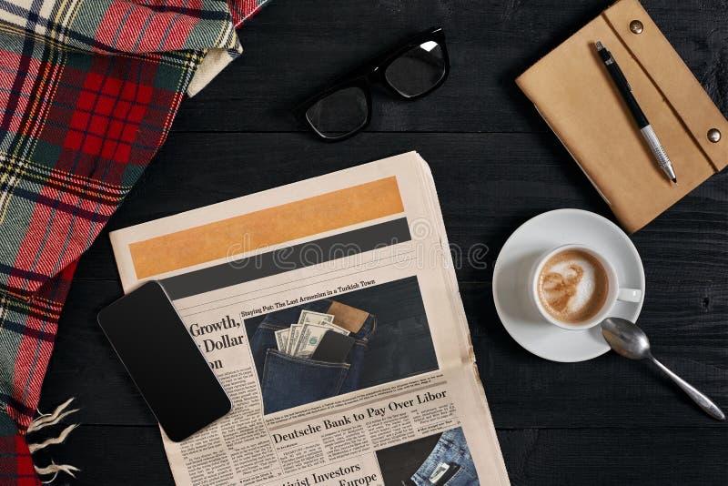 Boven mening van Slimme telefoon, krant, sjaal in een kooi, glazen met notitieboekje en kop van lattekoffie op zwarte houten stock afbeeldingen