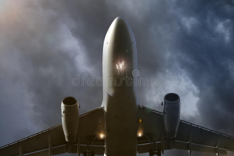 boven vliegend vliegtuig in avondwolken stock foto
