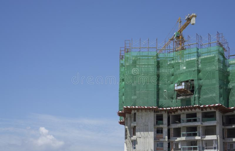 Bovenaanzicht van de afdekking van het voorgebouw door het groene net, de grote Tall Tower Crane bewegende machine in bouwwerkzaa royalty-vrije stock foto's