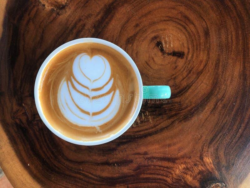 Bovenaanzicht van de hartvorm latte kunstkoffie in groen en wit bekertje op de oude houten tafel stock afbeelding