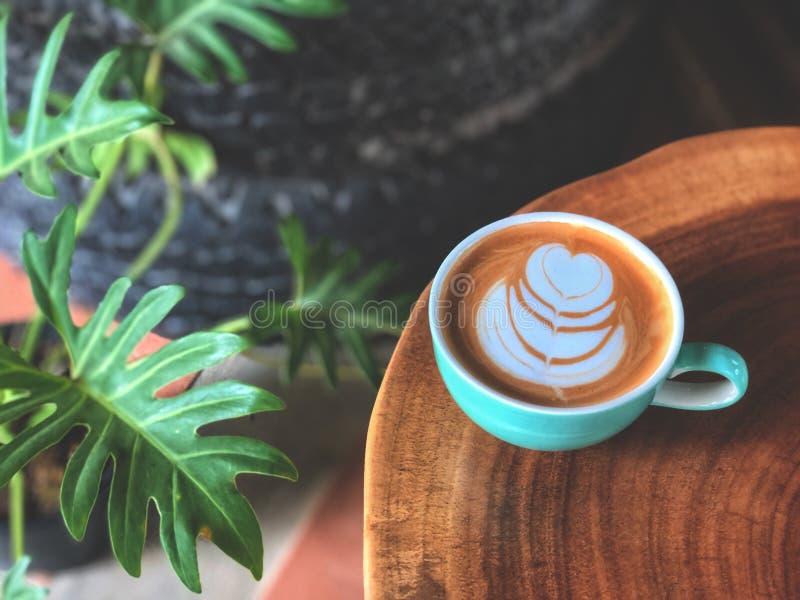 Bovenaanzicht van de hartvorm latte kunstkoffie in groen en wit bekertje op de oude houten tafel met groen verlof royalty-vrije stock foto's