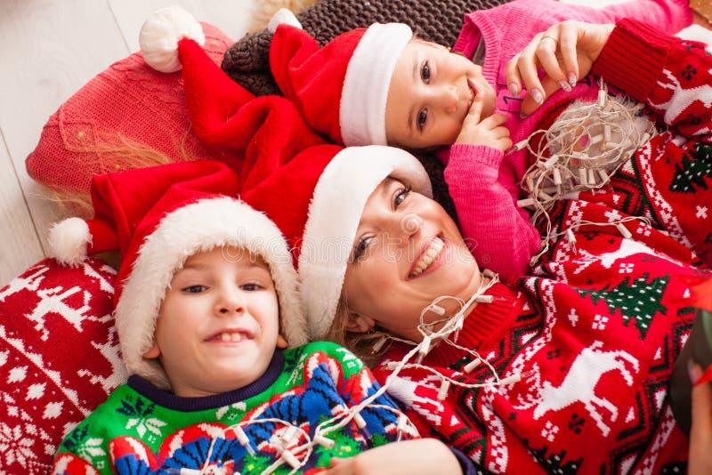 Bovenaanzicht van gelukkige moeder met dochter en zoon in Santa Hats terwijl ze thuis op de vloer ligt royalty-vrije stock afbeeldingen