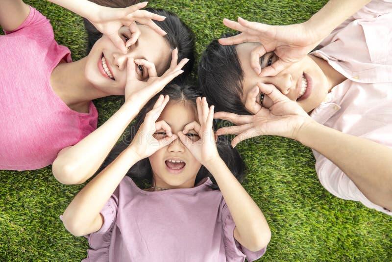 Bovenaanzicht van Happy Young Family op het gras ligt royalty-vrije stock foto