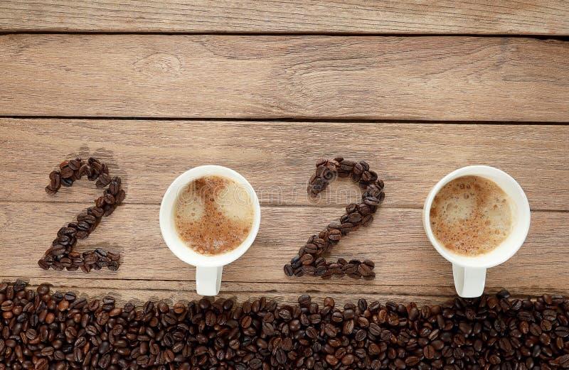 Bovenaanzicht van koffiebonen en warme verse koffie in een witte beker met schuim en tekst 2020 voor Happy NieuwYear Concept op h royalty-vrije stock afbeeldingen