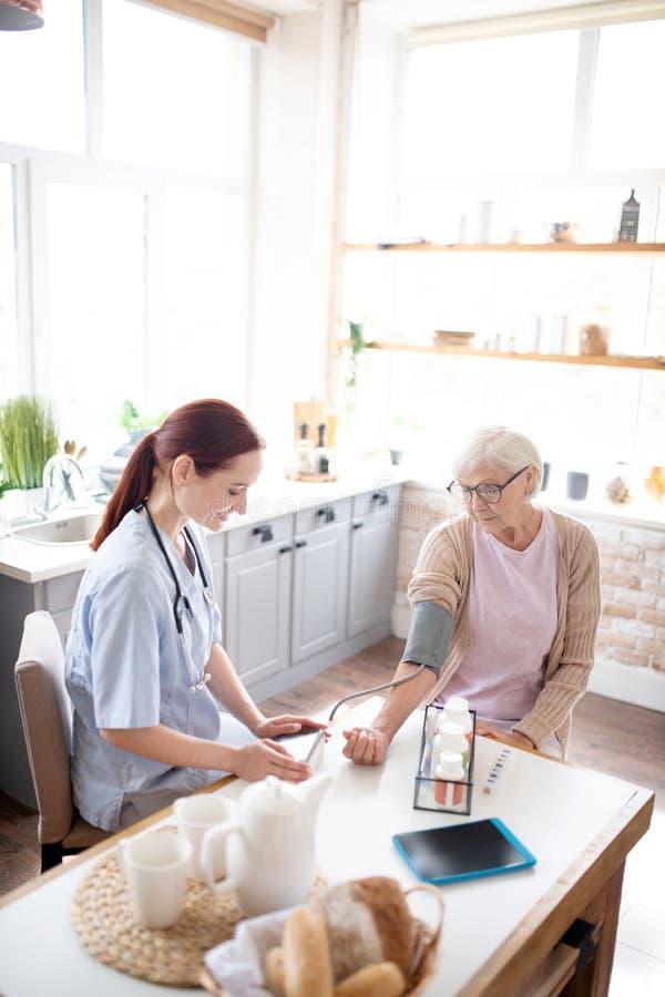 Bovenaanzicht van verpleegkundige die druk voor gepensioneerde meet royalty-vrije stock afbeeldingen