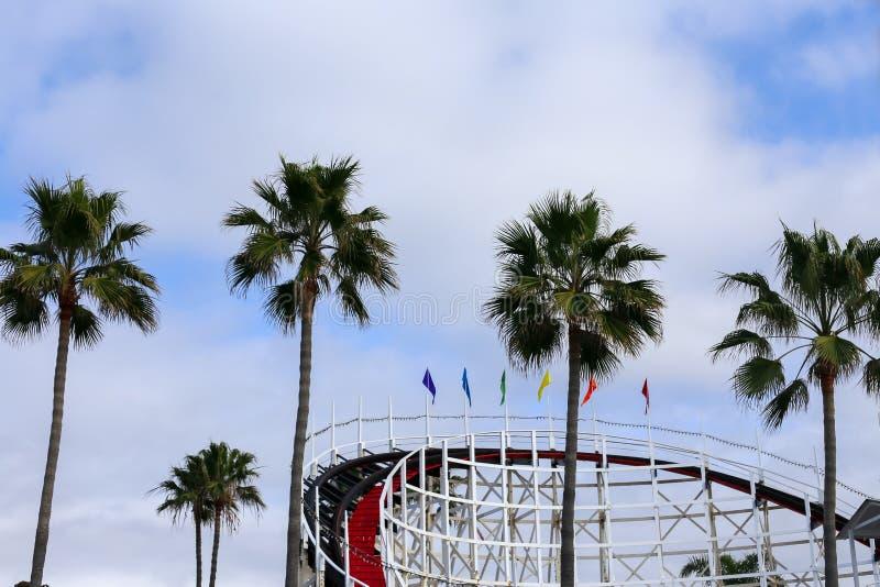Bovenkant van achtbaan en palmen en bewolkte blauwe hemel stock afbeelding