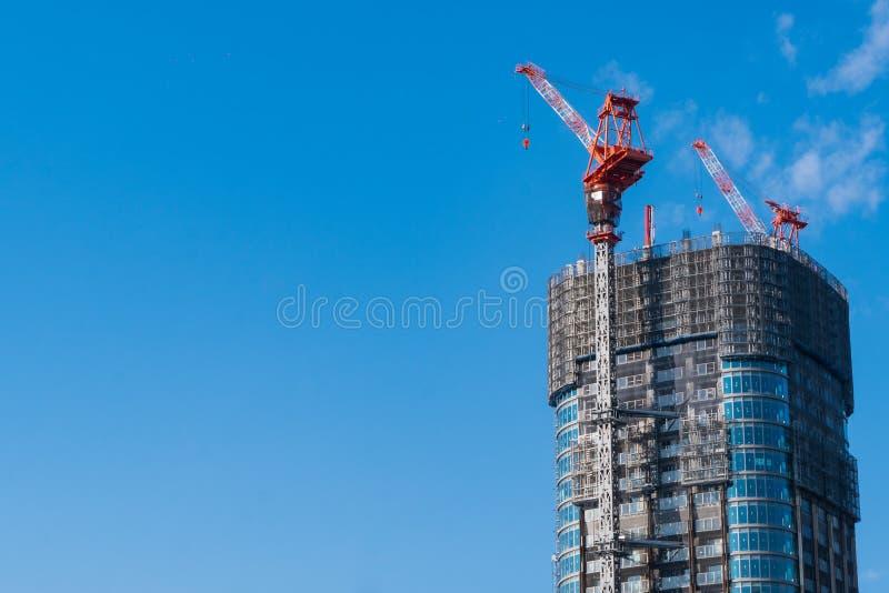 Bovenkant van bouwwerf met kranen op blauwe hemelachtergrond met exemplaarruimte stock fotografie