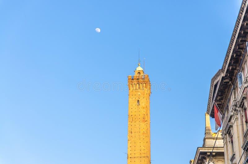 Bovenkant van de middeleeuwse toren van Garisenda van Bologna en maan met blauwe hemelachtergrond in vroege avond royalty-vrije stock afbeeldingen