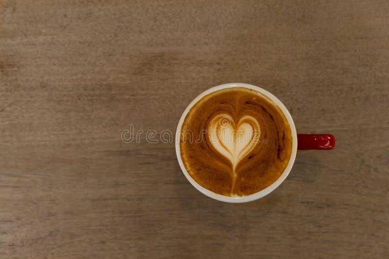 Bovenkant van de witte drank van de de cappuccinokoffie van de hartvorm hete in rode ceramische kop op houten lijstachtergrond stock fotografie