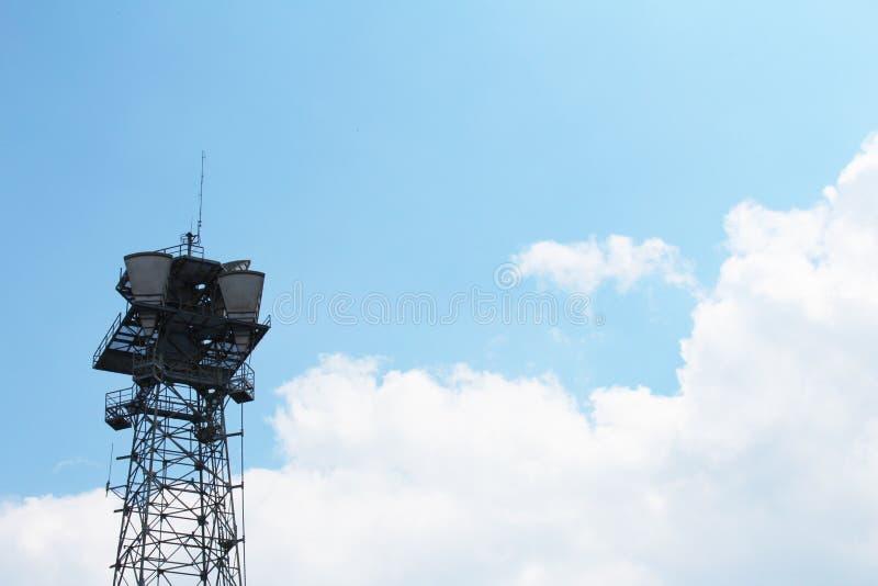 Bovenkant van een cel communicatie antennetoren tegen een blauwe hemel met wolken stock foto