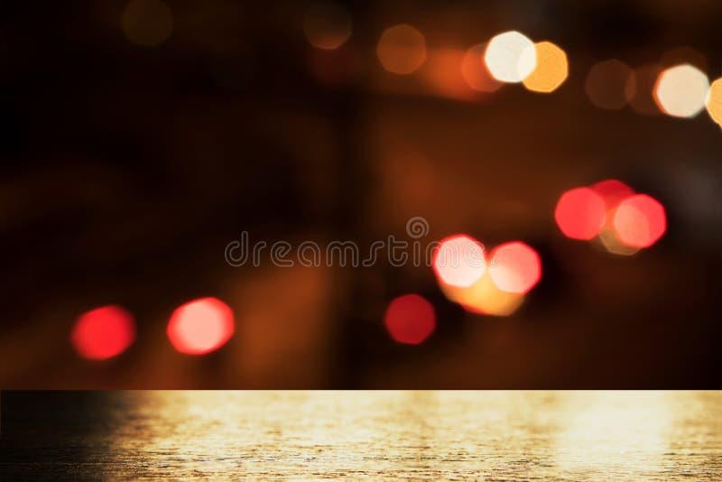 Bovenkant van gouden licht op houten lijst met rood oranje bokehlicht van de onduidelijk beeldstad op de donkere nachtachtergrond royalty-vrije stock fotografie