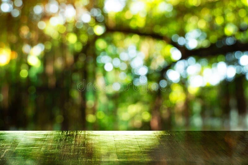 Bovenkant van houten lijst met lichte boom van de onduidelijk beeld de groene zomer op bostuinachtergrond royalty-vrije stock afbeeldingen