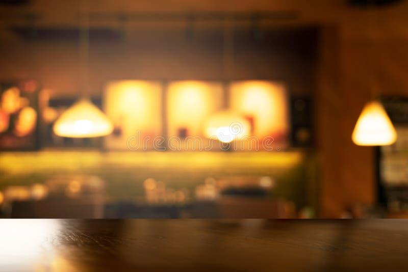 Bovenkant van houten lijst met onduidelijk beeld drie lamp in barkoffie en restaurant bij nacht binnenlandse achtergrond stock foto's