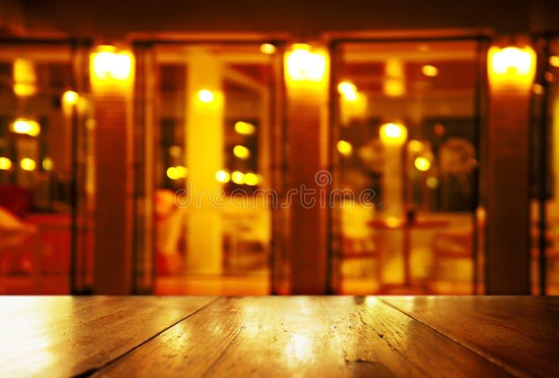 Bovenkant van houten lijst met onduidelijk beeldbar en bar in donkere nacht stock afbeelding