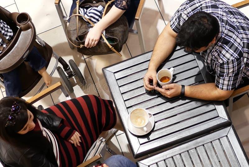 Bovenkant van klant het drinken koffie wordt geschoten en het babbelen met vriend die stock foto