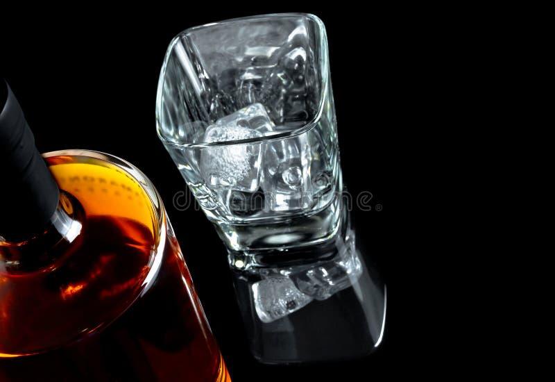 Bovenkant van mening van leeg whiskyglas met ijs dichtbij fles op zwarte achtergrond royalty-vrije stock foto's