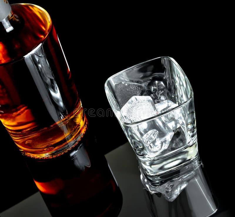 Bovenkant van mening van leeg whiskyglas met ijs dichtbij fles op zwarte achtergrond stock foto