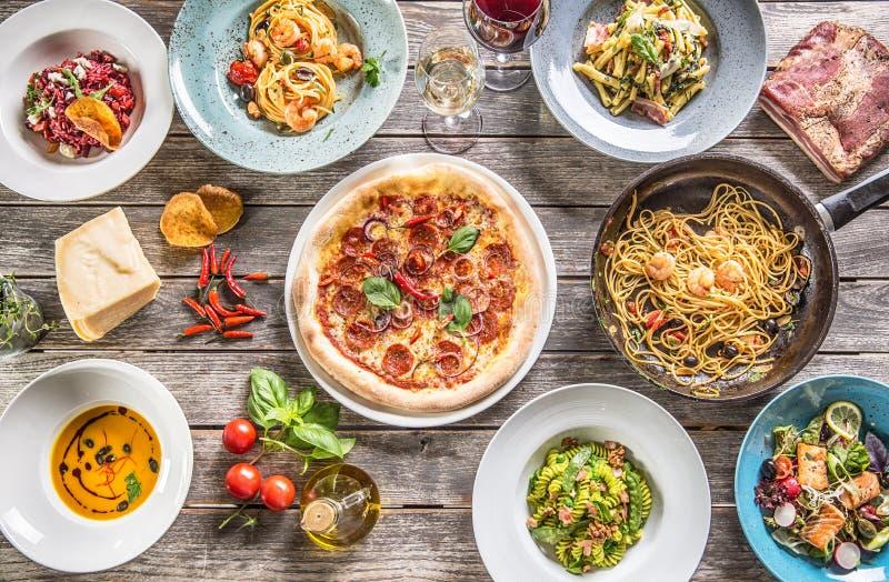 Bovenkant van menings volledige lijst van Italiaanse maaltijd op platen en pan Risottosoep van pizzadeegwaren en vissen plantaard royalty-vrije stock foto's