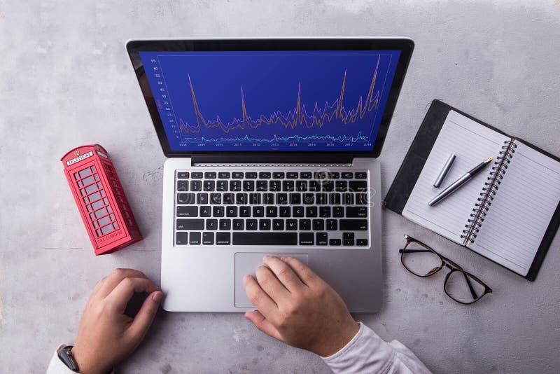 Bovenkant van zakenman die laptop computer met de markt van de voorraadgrafiek op het scherm met behulp van stock fotografie