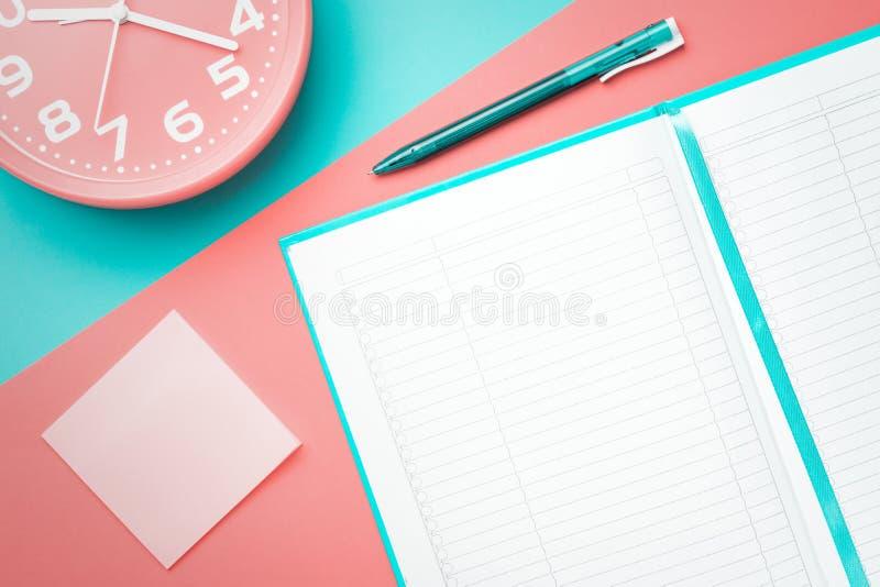 Bovenkant viewnotebook met een pen en een klok en een sticker op een gekleurde achtergrond royalty-vrije stock afbeelding