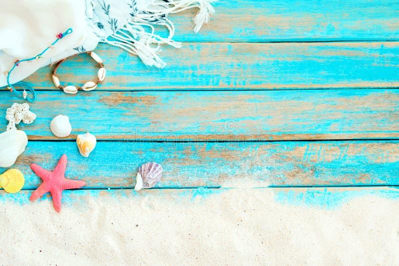 Bovenkant viwe van strandzand met witte die sjaal, armband van zeeschelpen wordt gemaakt, zeester, shells en koraal op blauwe hou stock foto
