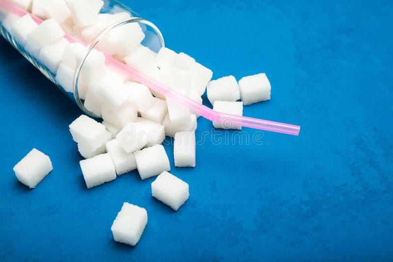 Bovenmatige suiker in een los glas op een blauwe achtergrond, concept stock afbeeldingen