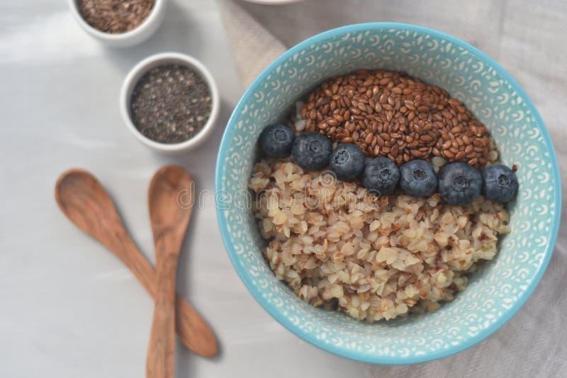 Bovetehavregröt i en bunke med linfrö och blåbär bantar frukosterar sund mat för oncept, detox, royaltyfria bilder